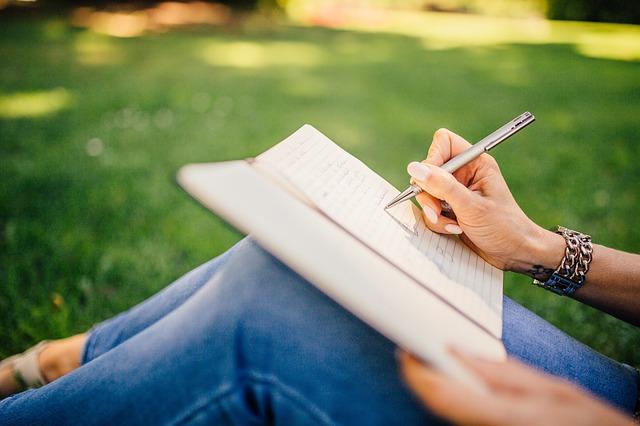 野原でノートに落書きを書く